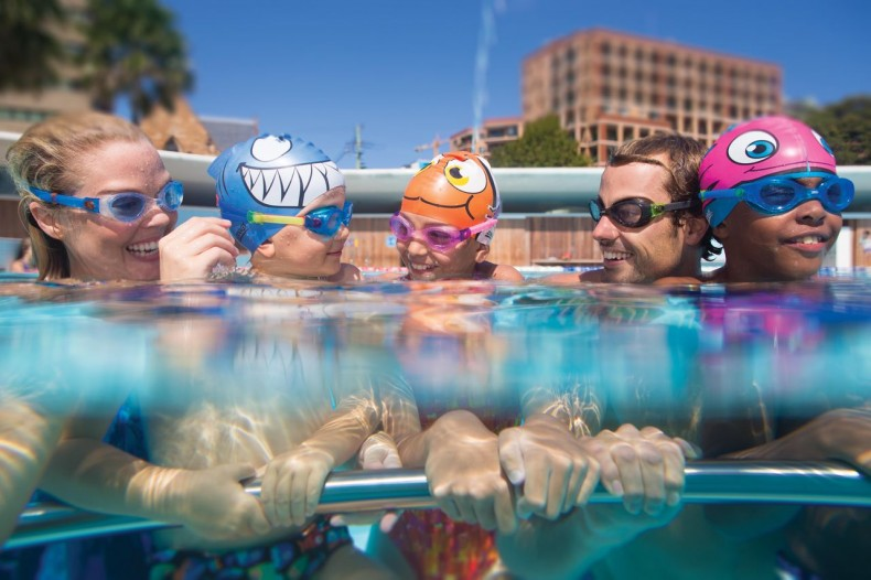 family in swimming pool wearing Zoggs goggles - swimming lessons