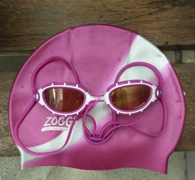 Swimming Cap and Goggles on the side of the pool