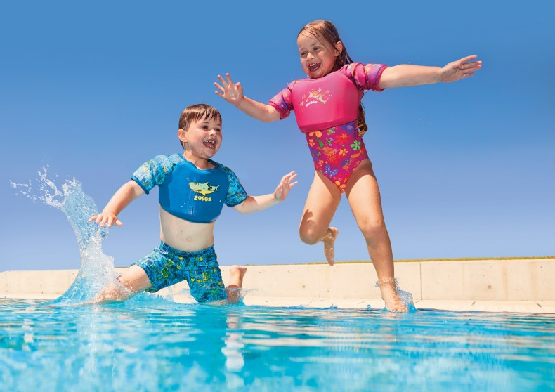 Two kids jumping into the pool wearing their water wing vest