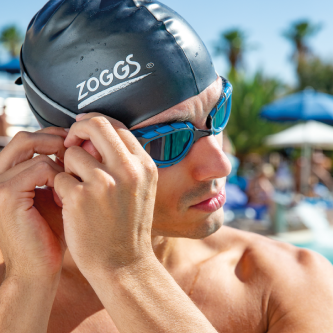Man wearing a swim cap and adjusting his goggle