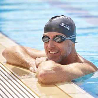 Man in the pool wearing a black cap and goggle