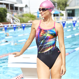Women standing at the pool edge and wearing a colorful swimsuit, a pink cap and a goggle