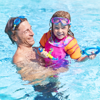 Man carry his daughter in the pool