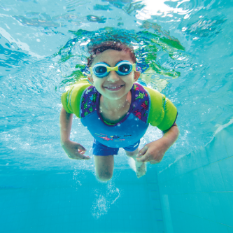 Boy wearing a water wings vest and is diving in the pool