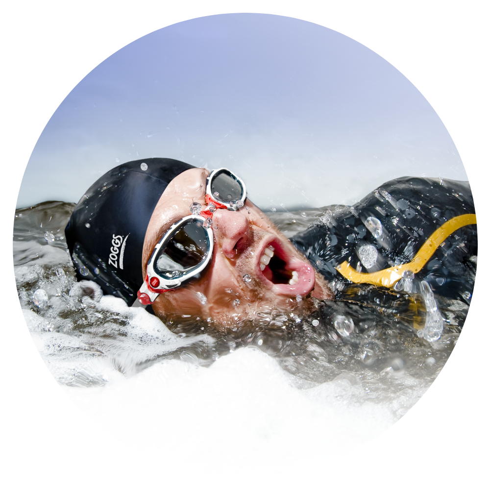 Man wearing swimming cap and goggle is swimming in the sea