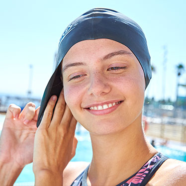 Woman putting on a swimmin cap and google