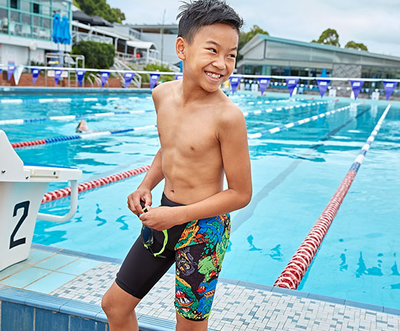 Boy wears a blue swim short and is jumping