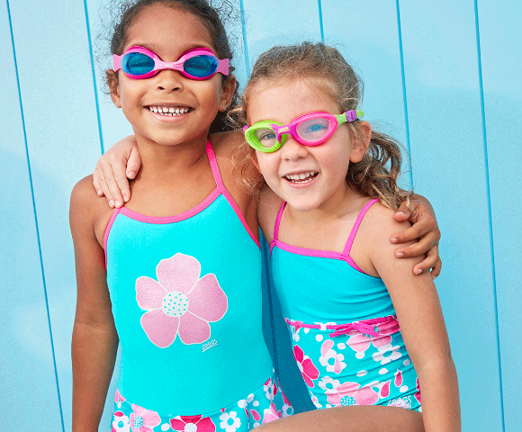 Two girls wearing blue/pink flowered swimsuits and goggles