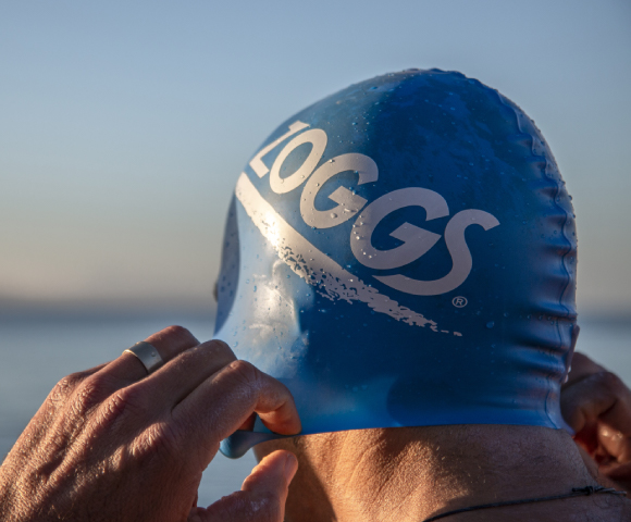 Backside of a men who is putting on a blue Zoggs cap