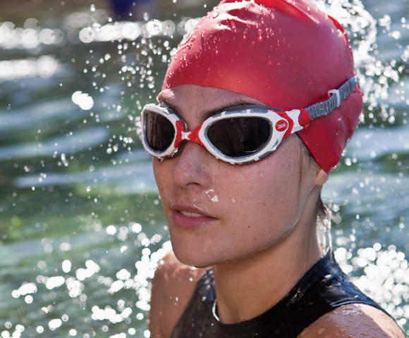 Woman in the open water wearing a red cap and a open water goggle of Zoggs