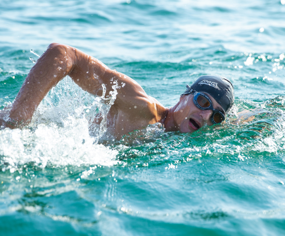 Man is swimming in the open water and wears a goggle and a cap of zoggs
