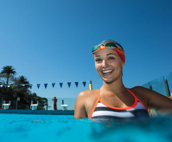 Women in the pool wearing a blue white striped swim suit as well as a swim cap and google