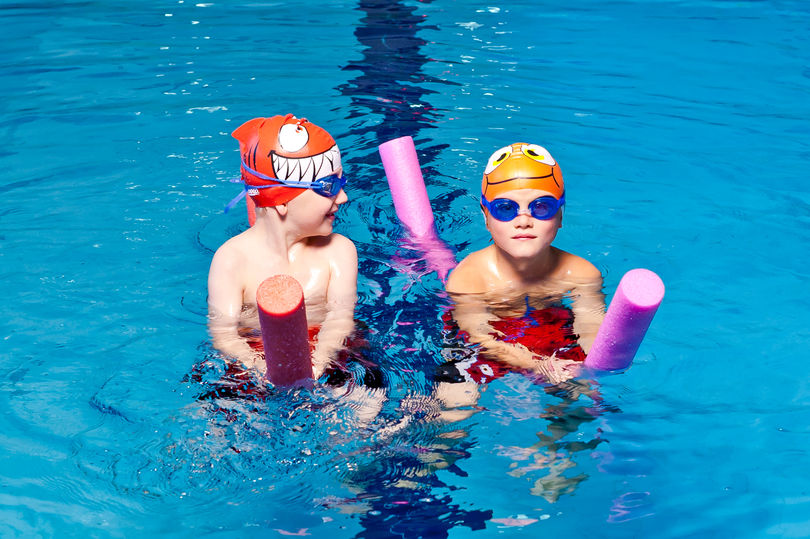 Two kids wering caps and googles are swimming in the pool