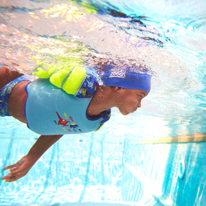 Girl who wears the water wings vest during diving